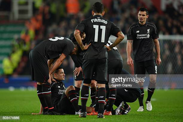 Philippe Coutinho of Liverpool receives treatment before leaving the pitch due to the injury during the Capital One Cup semi final first leg match...