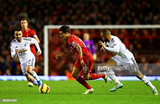 Philippe Coutinho of Liverpool runs with the ball past Ashley Richards and Leon Britton of Swansea City during the Barclays Premier League match...