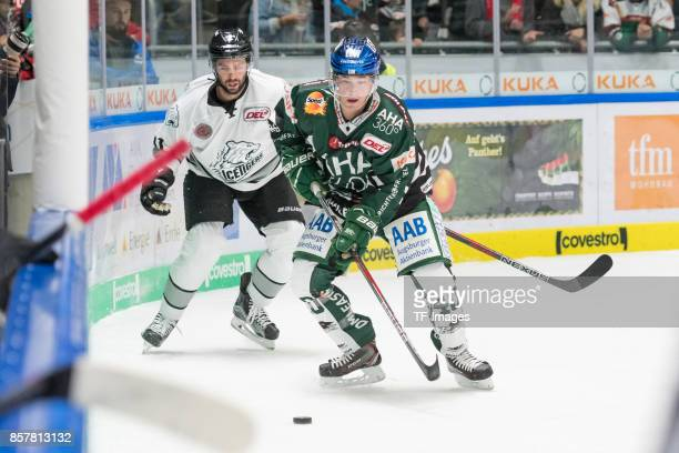 Philippe Dupuis of Nuernberg Ice Tigers and Evan Trupp of Augsburger Panther battle for the ball during the DEL match between Augsburger Panther and...