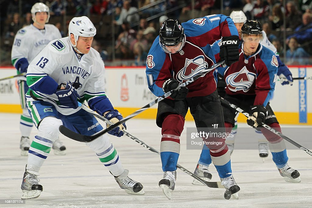 Philippe Dupuis of the Colorado Avalanche controls the puck with his skate while under pressure from Raffi Torres of the Vancouver Canucks at the...