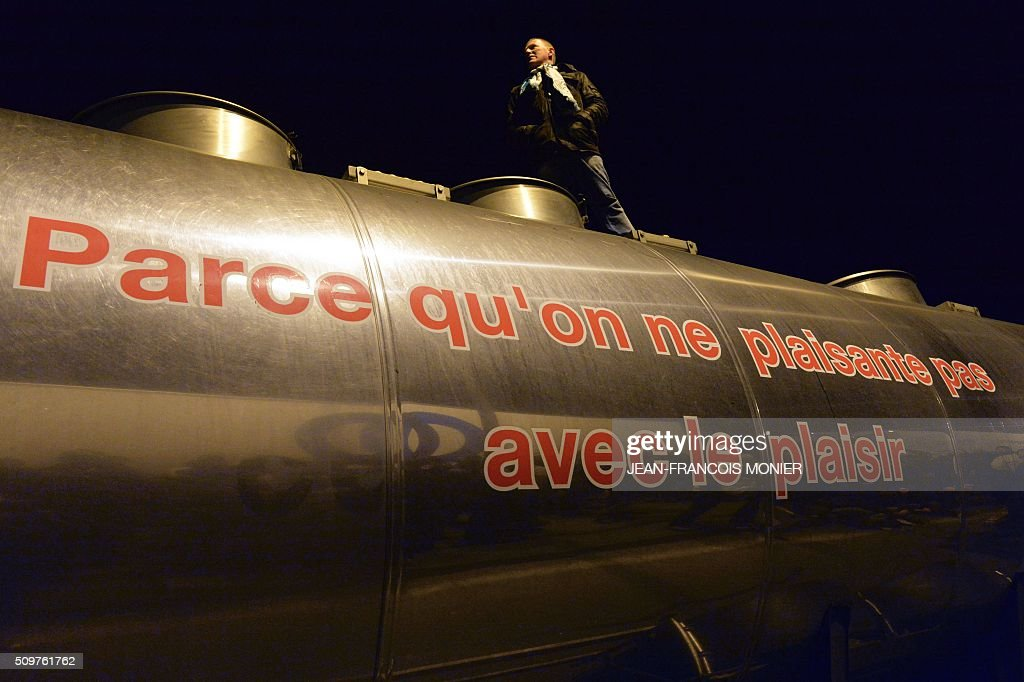 Philippe Jehan President of the FDSEA 53, a french farmer union, delivers a speech perched on a milk truck of the President group with a message reading 'Because we do not mess with Pleasure' as farmers block refrigerated trucks, including some transporting foreign meat on February 11, 2016, in Laval North-western France during a protest by farmers against the falling prices of agricultural products. / AFP / JEAN-FRANCOIS MONIER
