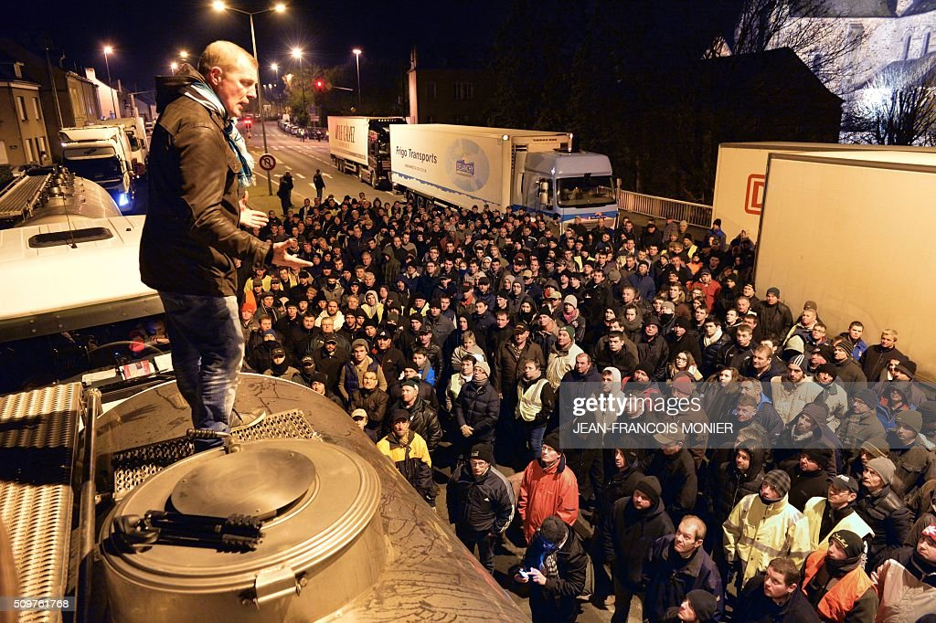 Philippe Jehan President of the FDSEA 53, a french farmer union, delivers a speech perched on a milk truck of the President group as farmers block refrigerated trucks, including some transporting foreign meat on February 11, 2016, in Laval North-western France during a protest by farmers against the falling prices of agricultural products. / AFP / JEAN-FRANCOIS MONIER