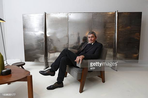Philippe Jousse founder of French Contemporary arts and design company Jousse Entreprise sits in front of Jean Prouve's Paravent made from bent steel...
