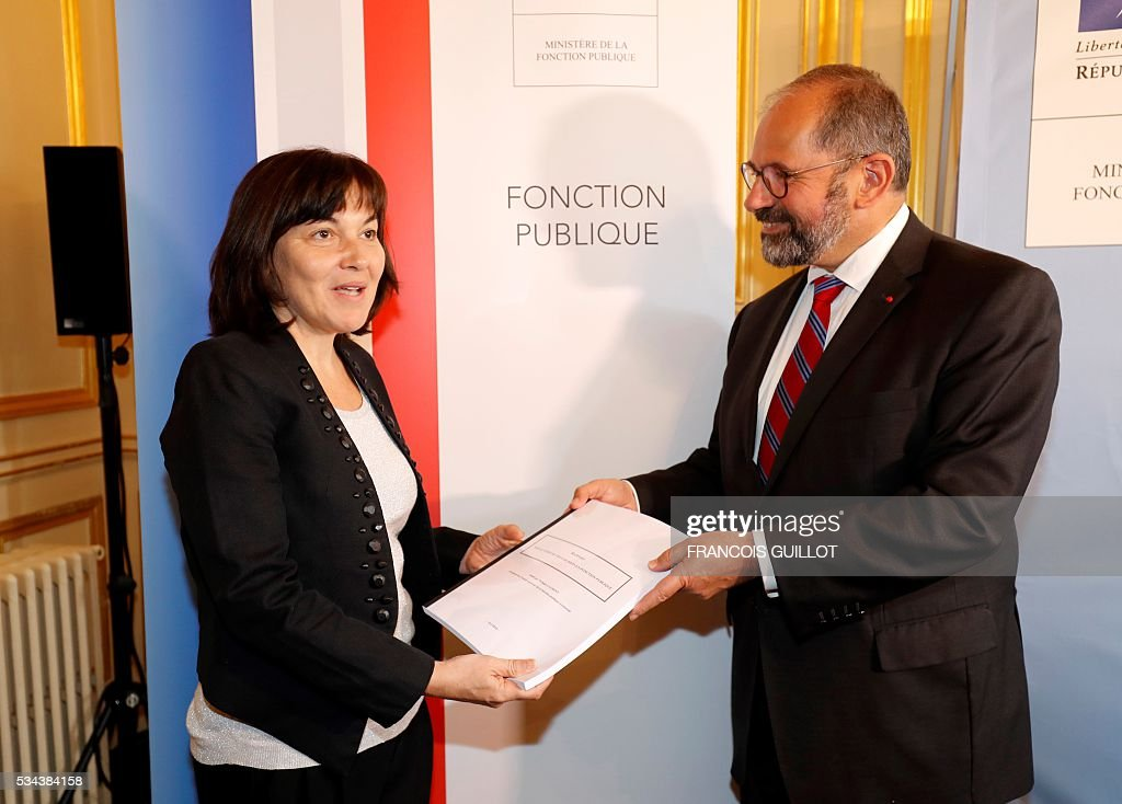 Philippe Laurent (R), mayor of the French town of Sceaux and the Union of Democrats and Independents (UDI) first president for the High Council of Public Affairs, presents Annick Girardin, minister of Public Affairs, a report on officials working hours on May 26, 2016 in Paris. / AFP / FRANCOIS