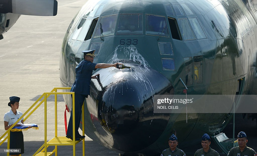 Philippine Air Force (PAF) Commanding General Lauro Catalino (C) pours champagne on the nose of a refurbished C-130B plane during a formal handover and blessing of the first ever locally maintained air and ground assets as part of a 14-million-USD maintenance project at the Philippines Air Force Villamor Air Base Grandstand in Manila on December 28, 2012. The Structural Maintenance Program (SMP) consists of a comprehensive program of inspection and preventive maintenace actions done in three-year intervals.