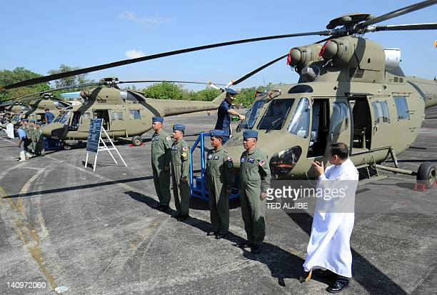 A Philippine airforce official pours champagne on one of the newlyacquired Sokol helicopters during a turnover ceremony at the former US airfield...