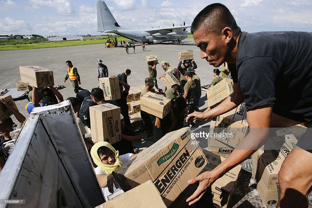 Philippine Army personnel unload relief goods to be transported to regions affected by Typhoon Bopha from the Marine Corps KC-130J Hercules millitary aircraft inside the International Airport in Davao, Mindanao on December 15, 2012. US Marines, the Philippine Armed forces and various non-profit organisations have been working together to provide humanitarian assistance and disaster relief support at the request of the Philippines government in the wake of Typhoon Bopha, which made landfall on December 4, 2012. The death toll from the strongest typhoon to hit the Philippines this year has climbed above 900, with hundreds still missing, the government said on December 13. AFP PHOTO / POOL / John Javellana