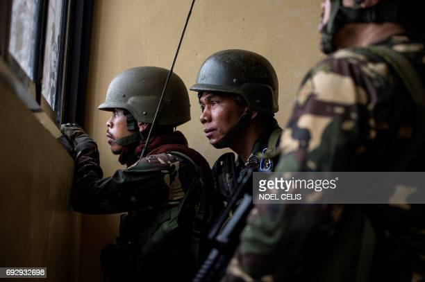 Philippine Army Scout Rangers peek from a school window during a mission to flush out Islamist militant snipers in Marawi on the southern island of...