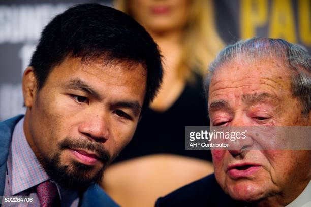 Philippine boxer Manny Pacquiao listens to boxing promoter Bob Arum during a press conference to promote the upcoming WBO welterweight title fight...