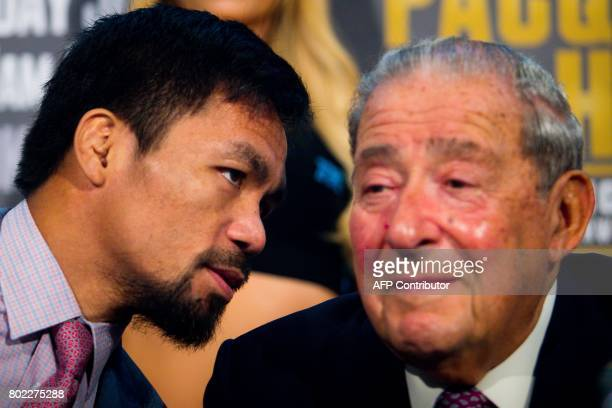 Philippine boxer Manny Pacquiao talks to boxing promoter Bob Arum during a press conference to promote the upcoming WBO welterweight title fight...
