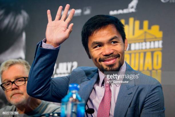 Philippine boxer Manny Pacquiao waves beside his trainer Freddie Roach during a press conference to promote the upcoming WBO welterweight title fight...
