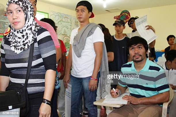 Philippine boxing icon and senatorial candidate Manny Pacquiao casts his ballot at a polling station in Kiamba Sarangani province on the southern...