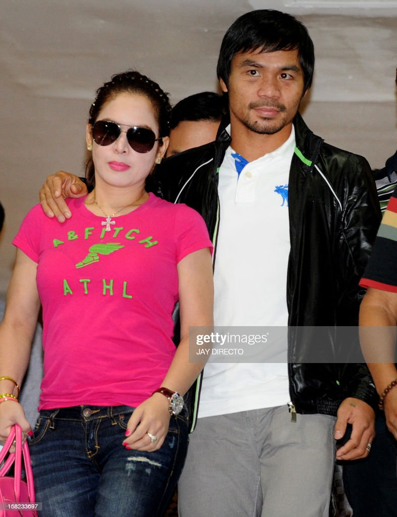 Philippine boxing icon Manny Pacquiao (R), accompanied by his wife Jinkee (L), arrives at Manila's international airport on December 12, 2012 on his return from the United States after his knockout loss to Mexican rival Juan Manuel Marquez in a non-title bout in Las Vegas on December 8. Pacquiao, who fought his way out of poverty as a teenager and is now immensely wealthy at the age of 34, had earlier controversially lost his World Boxing Organisation welterweight crown to unbeaten US fighter Tim Bradley on July 9 and is now facing calls by some to retire. AFP PHOTO / JAY DIRECTO