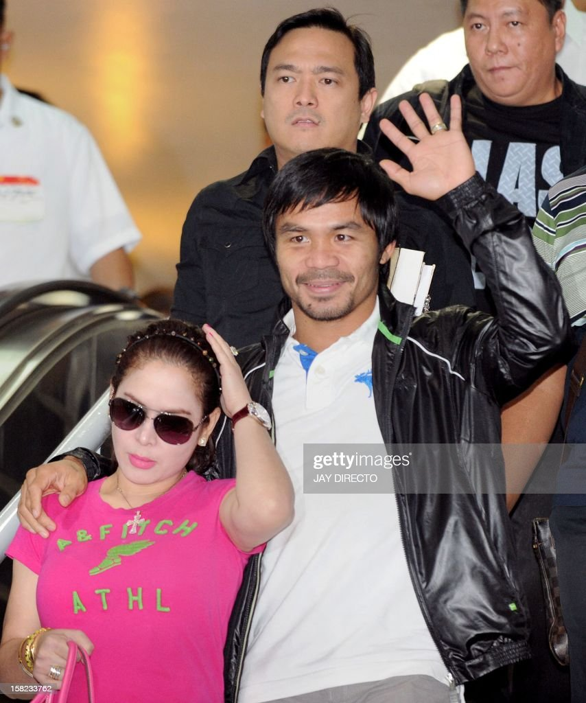 Philippine boxing icon Manny Pacquiao (R), accompanied by his wife Jinkee (L), waves to well-wishers upon his arrival at Manila's international airport on December 12, 2012 on his return from the United States after his knockout loss to Mexican rival Juan Manuel Marquez in a non-title bout in Las Vegas on December 8. Pacquiao, who fought his way out of poverty as a teenager and is now immensely wealthy at the age of 34, had earlier controversially lost his World Boxing Organisation welterweight crown to unbeaten US fighter Tim Bradley on July 9 and is now facing calls by some to retire.