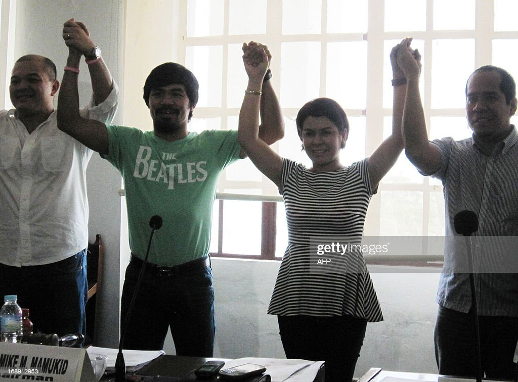 Philippine boxing icon Manny Pacquiao (2nd L) and his wife Jinkee (2nd R) are proclaimed by elections officials as winners in the just concluded mid-term elections, congressman and vice-governor respectively, during a ceremony in Alabel town, Sarangani province, on the southern island of Mindanao on May 16, 2013. More than 18,000 positions, from town councillors up to provincial governors and members of the legislature are being contested in the mid-term elections. AFP PHOTO / Paul Bernaldez