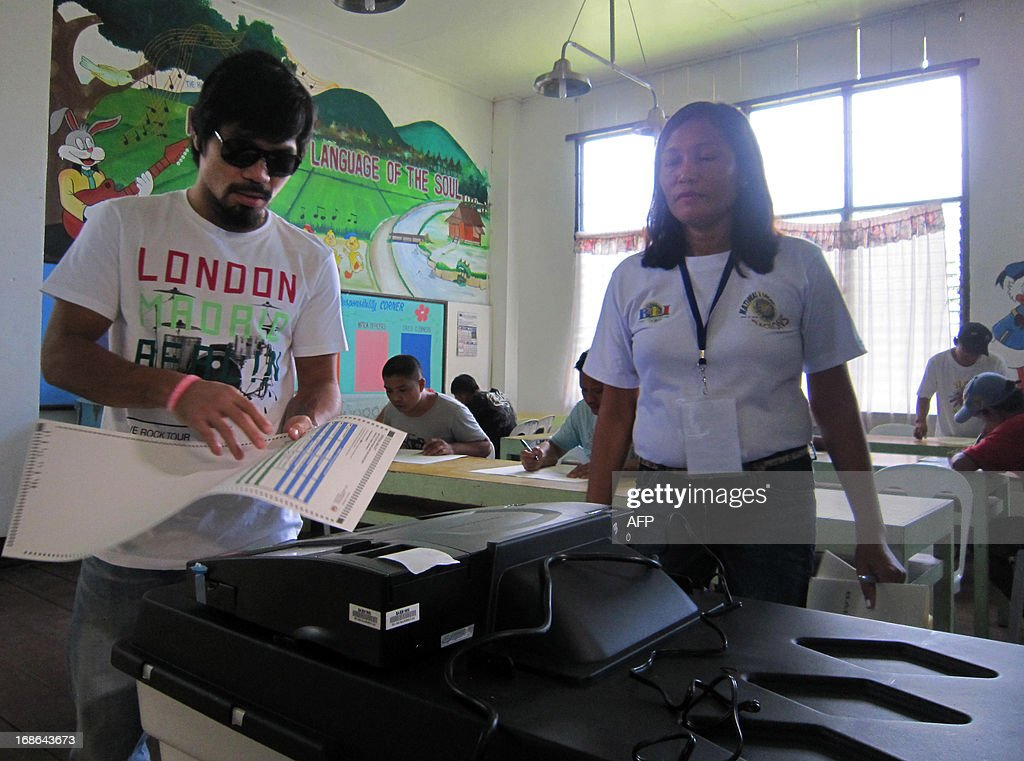 Philippine boxing icon, Manny Pacquiao, casts his vote during mid-term elections in Kiamba town, Sarangani province, in southern island of Mindanao on May 13, 2013. Paquaio is running for re-election as congreesman. The Philippines held elections May 13, seen as crucial for President Benigno Aquino's bold reform agenda, as deadly violence and graft-tainted candidates underlined the nation's deep-rooted problems. AFP PHOTO/Paul Bernaldez