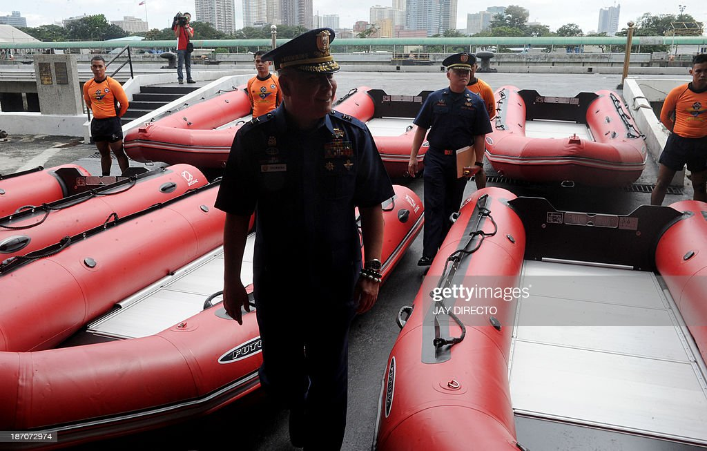 Philippine Coast Guard (PCG) Chief Rear Admiral Rodolfo Isorena (C) inspects newly-acquired rubber boats following a blessing ceremony in Manila on November 6, 2013. PCG Chief Rear Admiral Rodolfo Isorena ordered the newly-acquired rubber boats to be deployed to the central Philippines in preparation for the super typhoon Haiyan which is expected to make a landfall in that area on November 8. The Philippines is preparing for what it believes will be the most powerful typhoon to hit this storm-ravaged country this year. AFP PHOTO / Jay DIRECTO