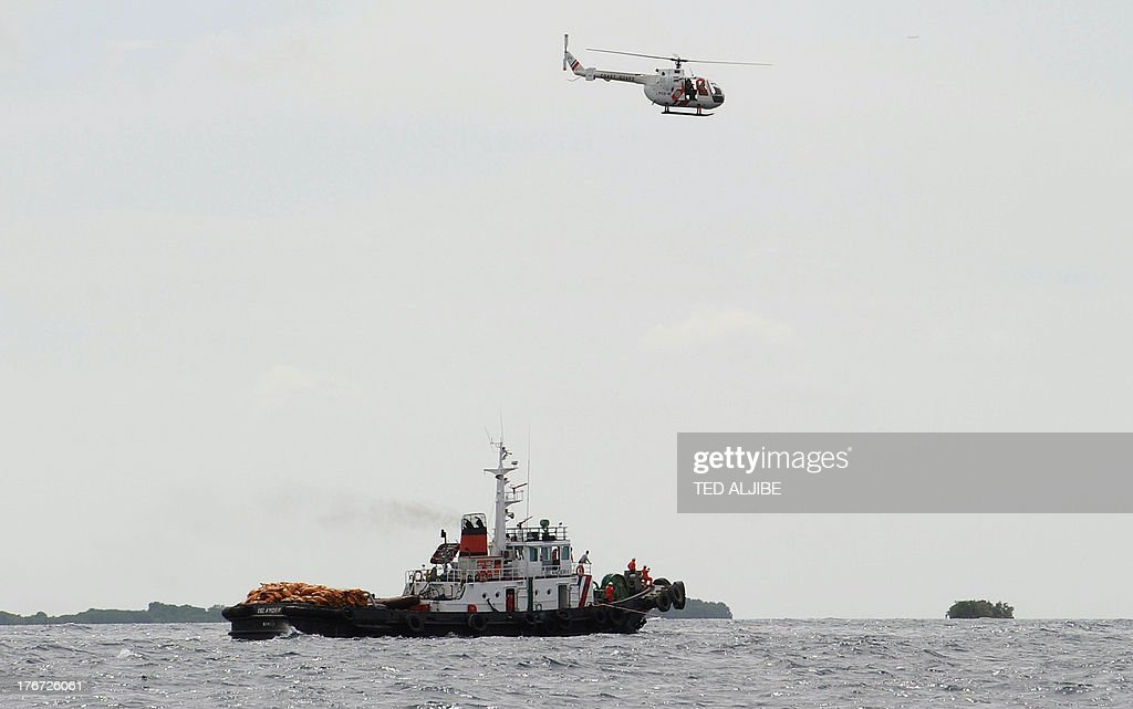 A Philippine Coast Guard helicopter hovers on August 18, 2013 above the site where a ferry collided with a freighter in Talisay near the central Philippine city of Cebu. Philippine rescuers struggled in rough seas on August 18 as they resumed a bleak search for 85 people missing in the country's latest ferry disaster, but insisted miracle survivor stories were possible. AFP PHOTO / TED ALJIBE