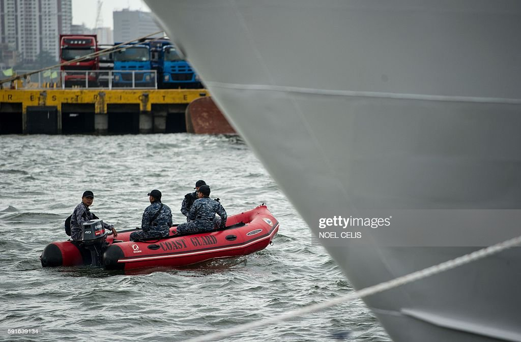 Philippine Coast Guard personnel in rigidinflatable boats patrol the harbour as the first ever multirole response vessel called the BRP Tubbataha...