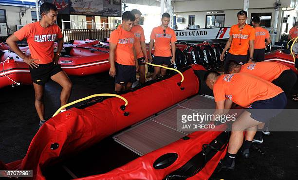 Philippine Coast Guard personnel inflate newlyacquired rubber boats following a blessing ceremony in Manila on November 6 2013 PCG Chief Rear Admiral...