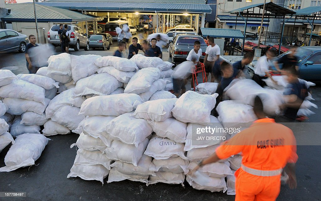 Philippine Coast Guard personnel prepare to carry relief goods for victims of Typhoon Bopha in New Bataan, Compostela Valley in the southern Philippines, on board a ship in Manila on December 6, 2012. A quarter million people were homeless and 477 confirmed dead after the Philippines' worst typhoon this year, officials said Thursday, as the government appealed for international help. Typhoon Bopha ploughed across Mindanao island on Tuesday, flattening whole towns in its path as hurricane-force winds brought torrential rain that triggered floods and landslides.