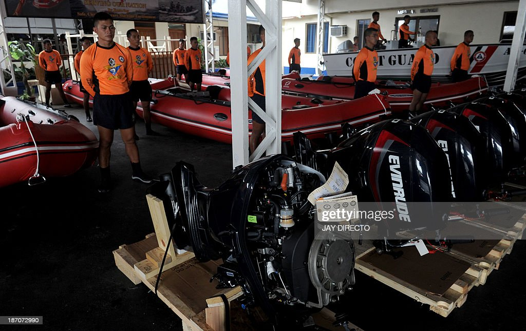 Philippine Coast Guard (PCG) personnel stand in formation beside newly-acquired rubber boats following a blessing ceremony in Manila on November 6, 2013. PCG Chief Rear Admiral Rodolfo Isorena ordered the newly-acquired rubber boats to be deployed to the central Philippines in preparation for the super typhoon Haiyan which is expected to make a landfall in that area on November 8. The Philippines is preparing for what it believes will be the most powerful typhoon to hit this storm-ravaged country this year. AFP PHOTO / Jay DIRECTO