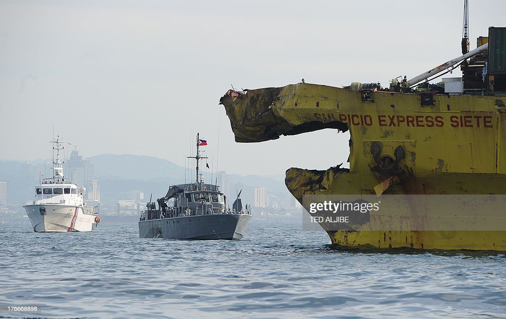 A Philippine Coast Guard ship (L) and Navy patrol boat (C) are anchored next to a damaged cargo ship on August 17, 2013 after it collided with the ferry St. Thomas Aquinas the night before off the town of Talisay near the Philippines' second largest city of Cebu. Philippine rescuers searched on August 17 for more than 200 people missing after the ferry collided with the cargo ship in thick darkness and sank almost instantly, with 26 already confirmed dead.