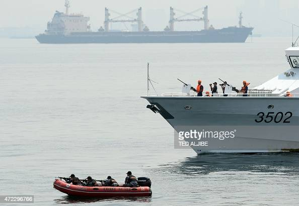A Philippine coastguard personnel aboard ship and a rubber boat take positions during a simulation of a sea jacking scenario as part of the combined...