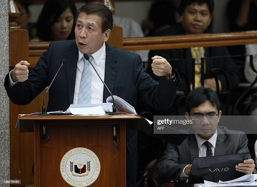 Philippine Congressman prosecutor Rudy Farinas (L) gestures while co-prosecutor Niel Tupas Jr. views a laptop during the impeachment trial of Supreme Court Chief Justice Renato Corona (not in photo) at the Senate in Manila on February 7, 2012. Corona is accused of violating the constitution in his efforts to protect graft-tainted former president Gloria Arroyo from prosecution, while also for allegedly amassing a personal fortune above the limits of his salary. AFP PHOTO / ROLEX DELA PENA / POOL