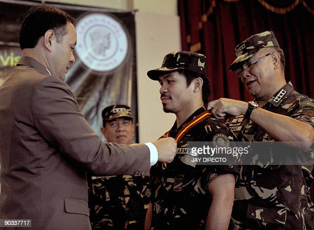 Philippine Defence Secretary Gilberto Teodoro and military chief General Victor Ibrado award a medal of 'outstanding achievement' to Philippine...