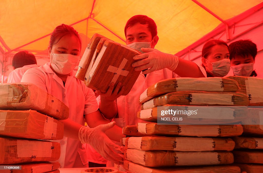 A Philippine Drug Enforcement Agency (PDEA) chemist checks a brick of seized marijuana before the marijuana and other dangerous drugs were destroyed using thermal decomposition in Manila on July 25, 2013. PDEA destroyed 22.33 million USD worth of dangerous drugs composed of methamphetamine hydrochloride, cocaine, marijuana, ecstasy, valium and expired medicines.
