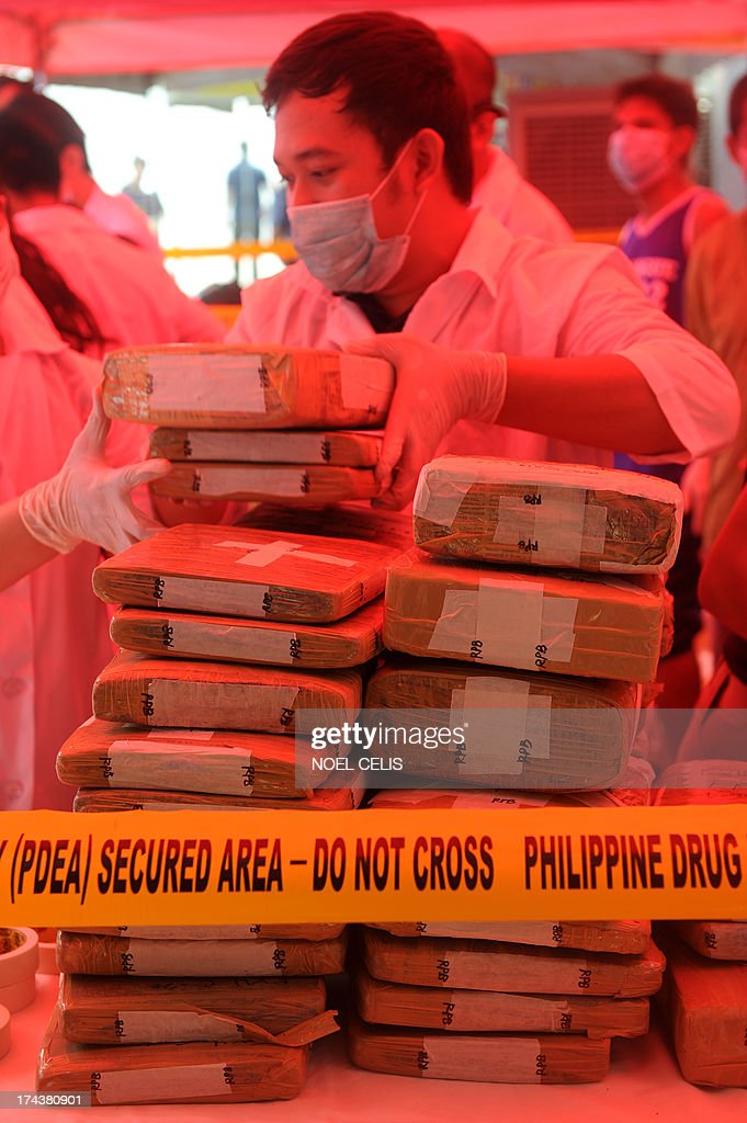 A Philippine Drug Enforcement Agency (PDEA) chemist checks a brick of seized marijuana before the marijuana and other dangerous drugs were destroyed using thermal decomposition in Manila on July 25, 2013. PDEA destroyed 22.33 million USD worth of dangerous drugs composed of methamphetamine hydrochloride, cocaine, marijuana, ecstasy, valium and expired medicines. AFP PHOTO/NOEL CELIS