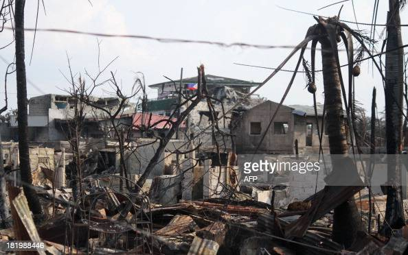 A Philippine flag flutters next to bulletriddled houses damaged by fire at the site of heavy fighting on the standoff between government forces and...