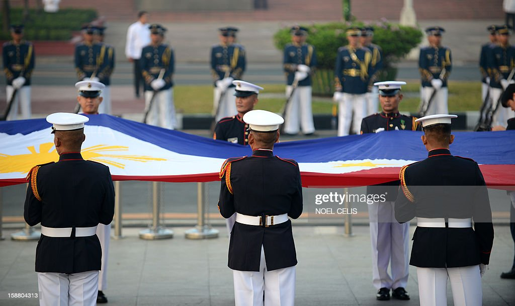 Philippine honour guards hold the national flag during a wreath-laying ceremony on the 106th anniversary of Philippine national hero Jose Rizal at the Luneta Park in Manila on December 30, 2012. Rizal was sentenced to death by a firing squad of the Spanish army after he was accused of leading a revolution against Spain.