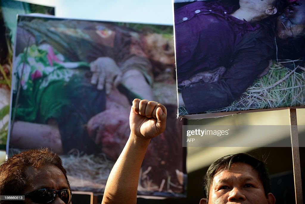 A Philippine journalist raises a clenched fists as they carry pictures of slain journalists during a protest at the Malacanang Palace in Manila on November 23, 2012, to commemorate the third anniversary of the November 23 Maguindanao massacre. Dozens of members of a clan whose leaders are on trial for the Philippines' worst political massacre are candidates in 2013 elections, some for the president's party, media and rights groups said November 23. The revelations sparked outrage on the three-year anniversary of the massacre, in which 58 people died, with critics saying the Ampatuan family's enduring political influence underlined the country's 'culture of impunity'. AFP PHOTO/NOEL CELIS