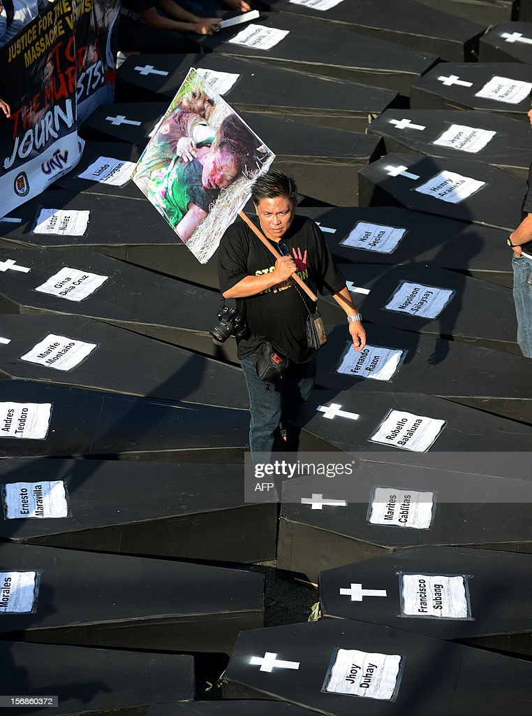 A Philippine journalist walks among mock coffins during a protest at the Malacanang Palace in Manila on November 23, 2012, to commemorate the third anniversary of the November 23 Maguindanao massacre. Dozens of members of a clan whose leaders are on trial for the Philippines' worst political massacre are candidates in 2013 elections, some for the president's party, media and rights groups said November 23. The revelations sparked outrage on the three-year anniversary of the massacre, in which 58 people died, with critics saying the Ampatuan family's enduring political influence underlined the country's 'culture of impunity'. AFP PHOTO/NOEL CELIS