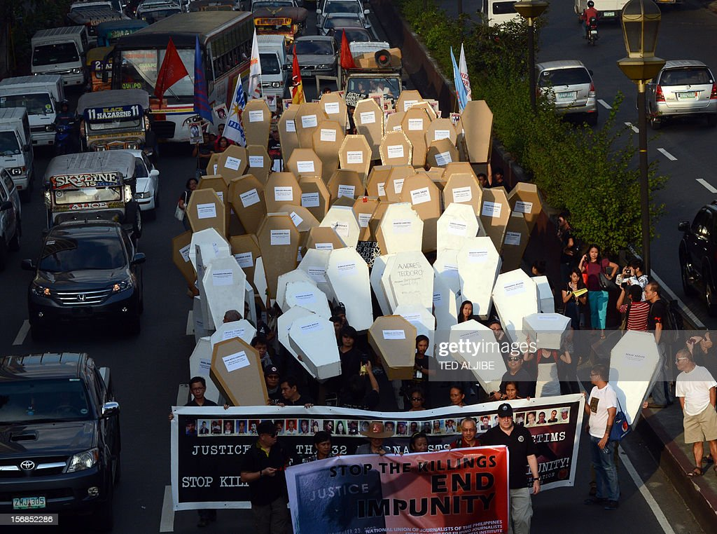 Philippine journalists and students carry mock coffins as they march towards Malacanang Palace in Manila on November 23, 2012, to commemorate the third anniversary of the November 23 Maguindanao massacre. Dozens of members of a clan whose leaders are on trial for the Philippines' worst political massacre are candidates in 2013 elections, some for the president's party, media and rights groups said November 23. The revelations sparked outrage on the three-year anniversary of the massacre, in which 58 people died, with critics saying the Ampatuan family's enduring political influence underlined the country's 'culture of impunity'. AFP PHOTO/TED ALJIBE