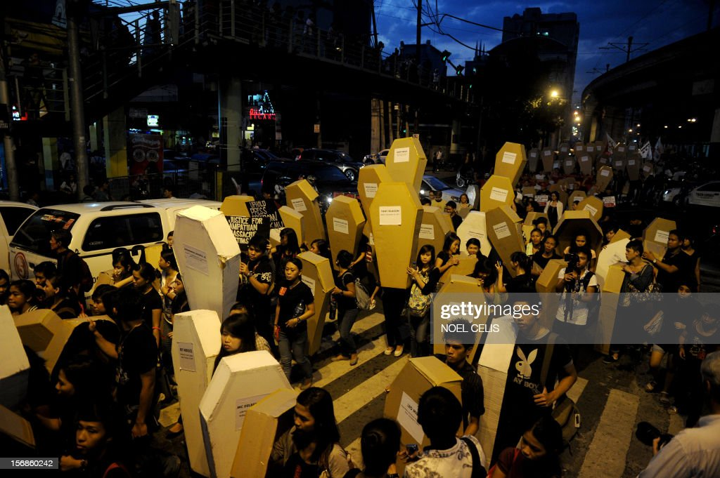 Philippine journalists and students carry mock coffins as they march towards Malacanang Palace in Manila on November 23, 2012, to commemorate the third anniversary of the November 23 Maguindanao massacre. Dozens of members of a clan whose leaders are on trial for the Philippines' worst political massacre are candidates in 2013 elections, some for the president's party, media and rights groups said November 23. The revelations sparked outrage on the three-year anniversary of the massacre, in which 58 people died, with critics saying the Ampatuan family's enduring political influence underlined the country's 'culture of impunity.'