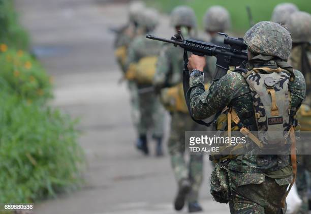 A Philippine Marine aims his assault rifle he and other Marines advance toward militant positions in Marawi on the southern island of Mindanao on May...
