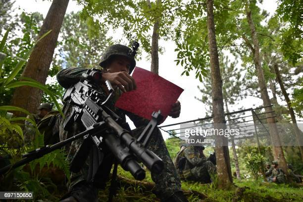 A Philippine Marine resting after having been at the frontline reads a letter sent by students in Marawi on the southern island of Mindanao on June...