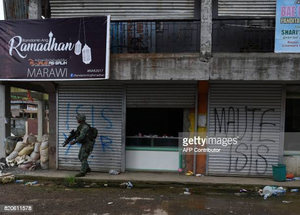 A Philippine Marine takes cover from sniper fire by Muslim militants during a patrol along a deserted street at the frontline in Marawi on the...