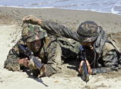 Philippine Marine uses sand to camouflage his colleague from the US Marines' 31st Marine Expeditionary Unit of the 3rd Marine Expeditionary Forces...