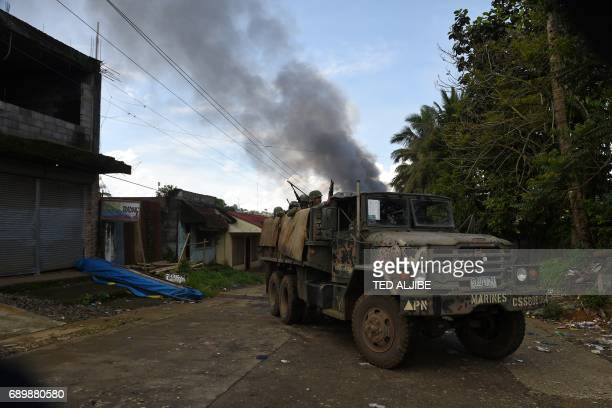 Philippine Marines aboard their truck drive past as smoke billows after military helicopters fired rockets at militant positions in Marawi on the...