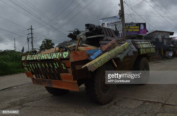 A Philippine marines armored personnel carrier with wooden planks to protect it from rocketpropelled grenade from Muslim militants speeds past a...