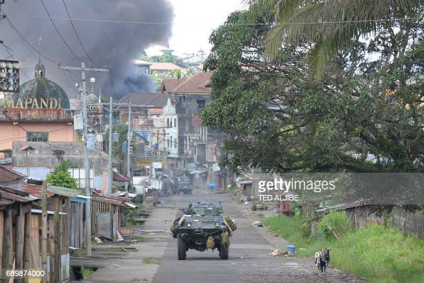 Philippine Marines armoured personnel carrier speeds away as black smoke billows from burning houses after military helicopters fired rockets at...