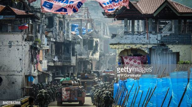 TOPSHOT Philippine Marines marching in formation alongside armoured personnel carriers head to the frontline past damaged buildings in the Mapandi...
