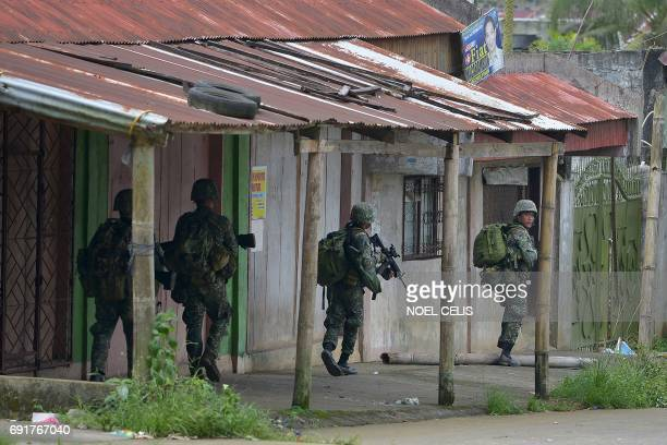 Philippine marines patrol a deserted street on their way to assault an Islamist militants' hideout in Marawi on the southern island of Mindanao on...