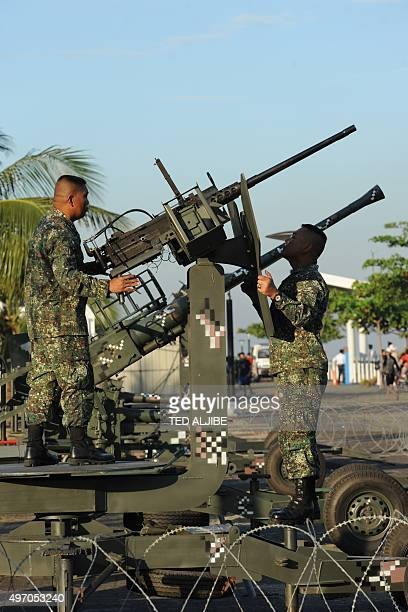 Philippine marines putting up barbed wire fence around antiaircraft guns deployed near the site of the AsiaPacific Economic Cooperation summit as...