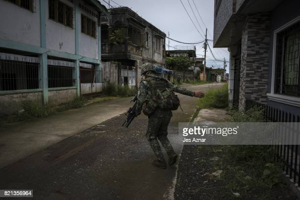 Philippine Marines soldiers in a cleared street but are still in range of enemy sniper fire as they walk towards the main battle area on July 22 2017...