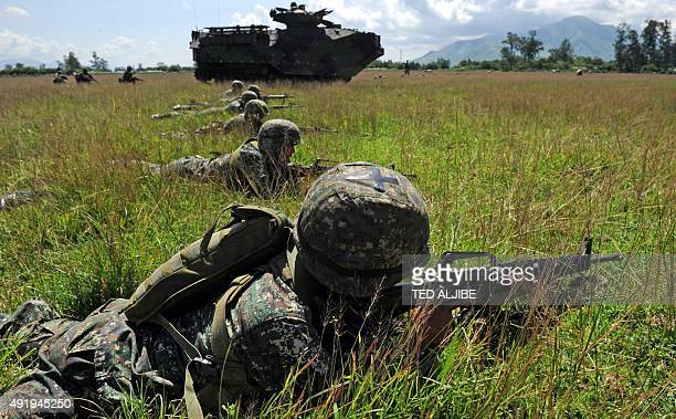 Philippine Marines take position next to a US Marine assault amphibious vehicles during a livefire exercise as part of the USPhilippines annual joint...